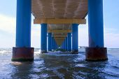 Sea Under Pier Among Parallel Blue Columns Making Narrow Corridor In Water. Seascape Through Pier Wi poster