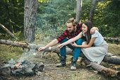 Friendship And Leisure Concept. Happy Couple Sitting Around Campfire. Young Couple In Love Having A  poster