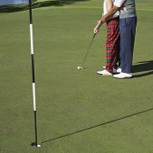 Постер, плакат: Человек помогают женщине удар на гольф поле