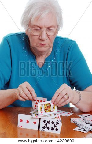 Elderly Woman Making A House With Playing Cards