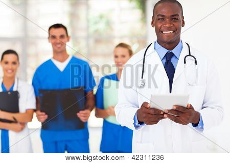 handsome african american medical doctor and team