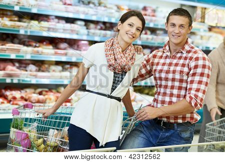 Young Family couple choosing bio food in grocery supermarket during weekly shopping
