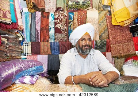 Portrait of Indian sikh man seller in turban with bushy beard at shawl shop