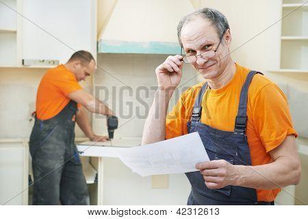 Portrait of Craftsman carpenter at kitchen cabinet installation service work