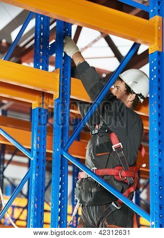 One warehouse worker in uniform with power tool during rack arrangement erection work