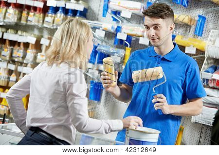 Assistant seller help buyer by demonstrating paint roller for painting at hardware store