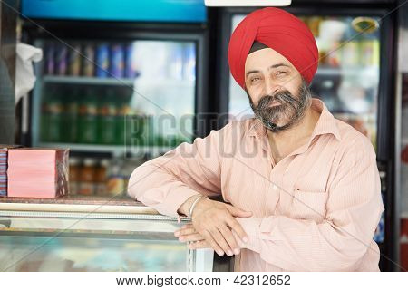 Portrait of Indian sikh man seller in turban with bushy beard at shop