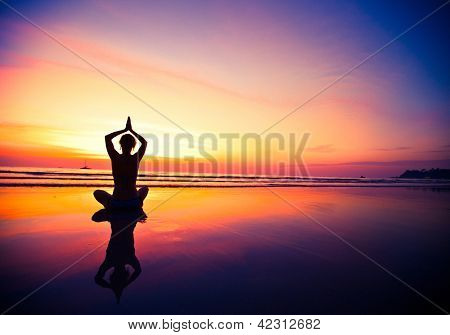 Yoga woman sitting on sea coast at sunset