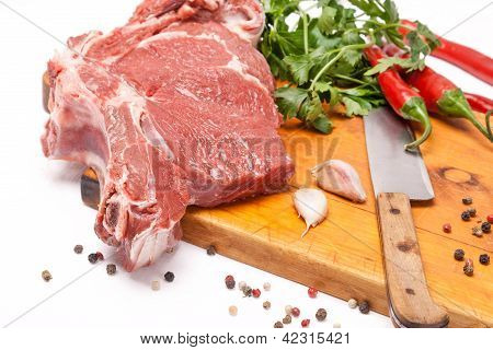 Fresh Meat Of Beef With Bone On Wooden Spices And Knife