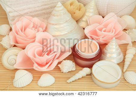 Bathroom accessories with rose spa soap petal buds and moisturising cream over bamboo background.