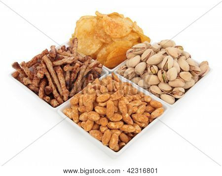 Potato crisps, pistachio nuts, roasted peanuts and twiglet savoury snacks in porcelain dishes over white background. Selective focus.