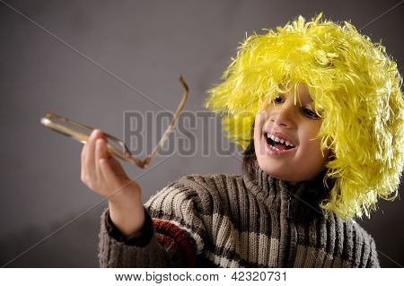 Closeup portrait of cute kid wearing yellow hair wig