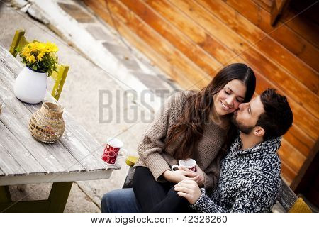 Young couple having breakfast in a romantic cabin outdoors in winter. He is kissing her cheek