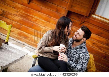 Jovem casal com café da manhã num chalé romântico ao ar livre no inverno.