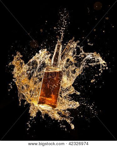 Concept of liquor splashing around bottle, isolated on black background