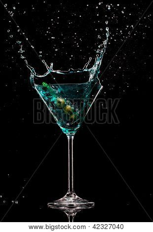Martini drink with splash, isolated on black background