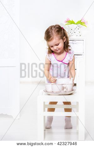 Tea time: little beautiful girl making tea