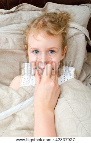 Portrait Of Little Girl Lying In Bed With Inhalator Mask On The Face