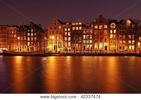 Medieval houses along the Amstel at night in Amsterdam the Netherlands