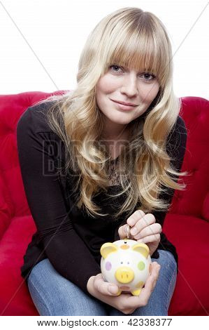 Young Blond Haired Girl Putting Coin In Piggybank On Red Sofa In Front Of White Background