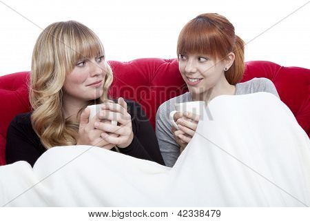 Young Beautiful Blond And Red Haired Girls On Red Sofa With Coffee Under Blanket In Front Of White B
