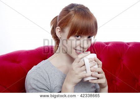 Young Beautiful Red Haired Girl On Red Sofa With Cup Of Tea In Front Of White Background