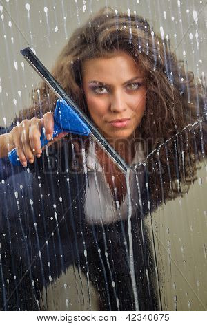 Young woman cleaning her windows with squeegee cleaning