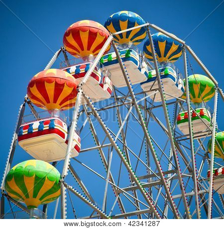 Close-up of colorful ferris wheel on vivid blue sky background