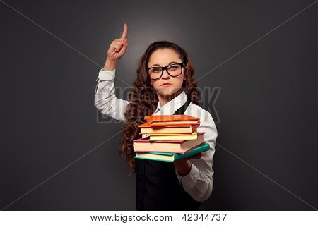 funny teacher in glasses with pile of textbooks. picture over dark background