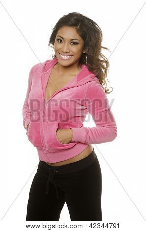 Gorgeous beautiful smiling young woman in casual sports track pants and pink hoodie isolated against white
