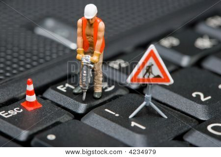 Miniature Figures Working On A Computer Keyboard