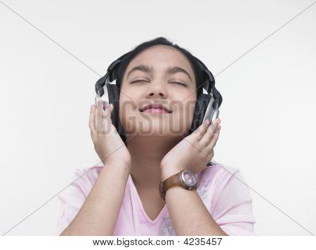 An Asian Girl Of Indian Origin Listening To Music