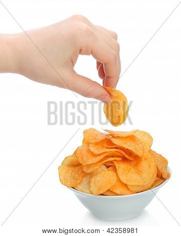 Hand holds a potato chip with the bowl of potato chips