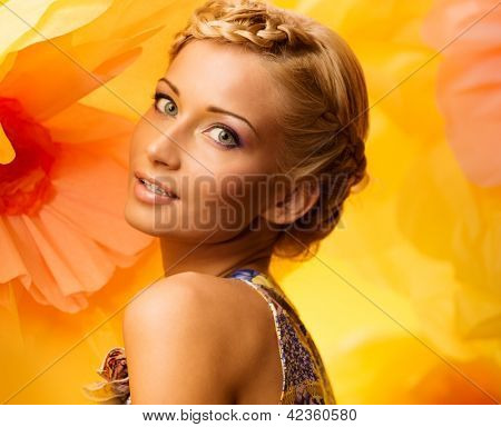 Beautiful young woman among big yellow flowers