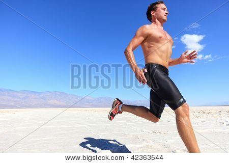 Athlete running sport - fitness runner sprinting in desert shirtless. Fit sports model man during sprint run at great speed under burning sun.