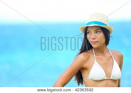Woman beach portrait looking to side with wearing hat and beachwear bikini. Beautiful young modern multiracial female model looking serious with subtle smile. Half asian and caucasian model outdoors.