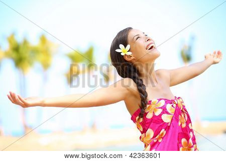 Free happy elated beach woman in freedom joy concept. Beautiful girl smiling with arms out looking up joyful on Hawaiian beach. Mixed race Asian / Caucasian girl.