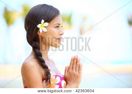 Serene meditation - meditating woman on beach smiling happy in profile on hawaiian beach. Beautiful portrait of mixed race Asian / Caucasian female model relaxing on Hawaii.