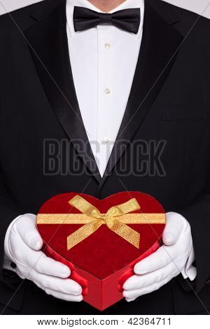 Man wearing black tie and white gloves holding a red heart shaped box of chocolates.