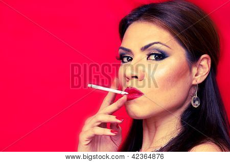 Close-up shot of a woman smoking cigar on the red background