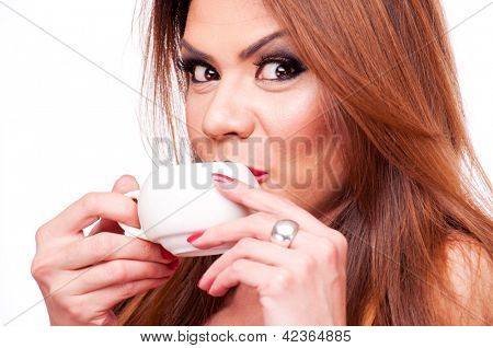 Beautiful woman drinking from white coffee cup, isolated on white