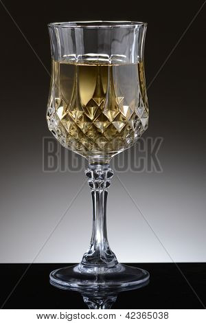 Closeup of a fancy glass of chardonnay wine on a light to dark gray background.