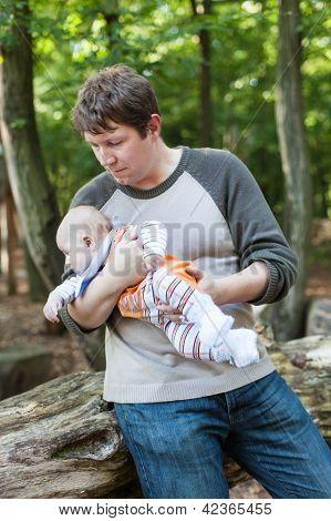 Young Father Carrying Son In Summer Forest