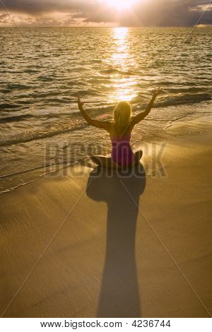 Fifty Year Old Woman Doing Yoga At Sunrise On The Beach