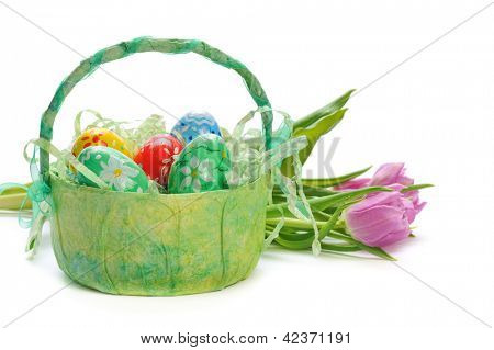 easter eggs in basket with tulips isolated on white background