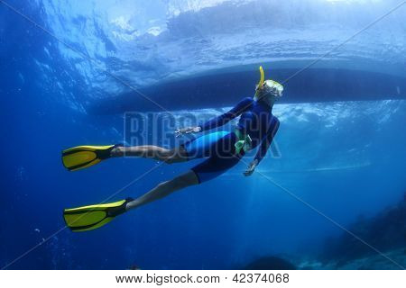 Underwater shoot of a young lady snorkeling and diving on a breath hold in a clear tropical sea