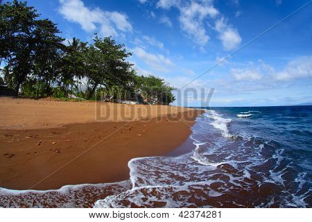 Tropical beach with dark volcanic sand and blue sea with waves. Dauin, Negros oriental, Philippines