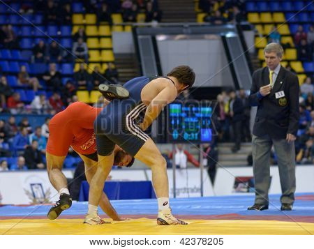 KIEV, UKRAINE - FEBRUARY 16: Match between Zubairov, Russia, red, and Turgaev, Kazakhstan during International freestyle wrestling and female wrestling tournament in Kiev, Ukraine on February 16, 2013