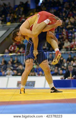 KIEV, UKRAINE - FEBRUARY 16: Match between Rabadanov, Russia, red and Aldatov, Ukraine during International freestyle wrestling and female wrestling tournament in Kiev, Ukraine on February 16, 2013