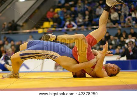 KIEV, UKRAINE - FEBRUARY 16: Match between Oganesyan, Russia, red and Magzumov, Kazakhstan during XIX International freestyle wrestling tournament in Kiev, Ukraine on February 16, 2013